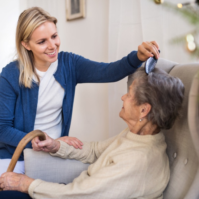Carer assisting senior woman