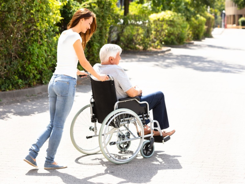 Carer assisting senior man